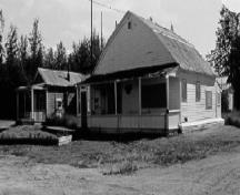 Corner view of the V.I.P. Guest House, showing the distinctive gambrel-like shape of the roof and the front verandah, 1988.; Parks Canada Agency / Agence Parcs Canada, 1988.