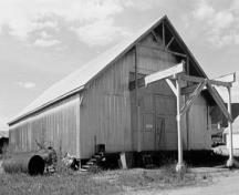 Corner view of Warehouse No. 3, showing the front double doors and the overhanging roof, 1988.; Parks Canada Agency / Agence Parcs Canada, 1988.