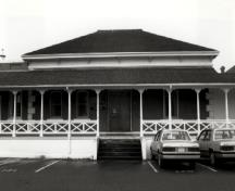 Façade of Building 37, showing its hipped roof, covered verandah, bracketed cornice and the segmentally-arched door and window openings with stone surrounds, 1989.; Ian Doull, Parks Canada Agency / Agence Parcs Canada, 1989.