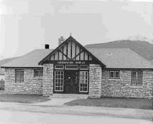 General view of the Rescue Building, showing the symmetrical placement of doors and small multi-paned casement windows, 1950.; Parks Canada Agency / Agence Parcs Canada, 1950.