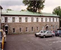 View of Building 1, showing the ground floor's solid masonry construction and the stucco finish of the upper storey, 1993.; Agence Parcs Canada / Parks Canada Agency, 1993.