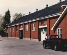 View of the exterior of RMC Building 3, showing the long, symmetrical, single-volume, pitched roof shed, 1993.; Parks Canada Agency / Agence Parcs Canada, 1993.
