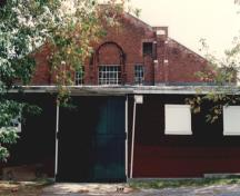 Exterior view of RMC Building 3, showing the former tack shed at the west end, 1993.; Parks Canada Agency / Agence Parcs Canada, 1993.