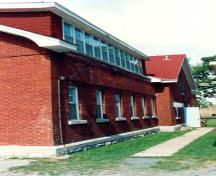View of the side façade of RMC Building 36, showing the stone base typical to the buildings of the immediate complex and other structures nearby, 1993.; Parks Canada Agency / Agence Parcs Canada, 1993.