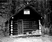 Front elevation of the Clearwater Lakes Warden Cabin, showing its six-pane windows with their muntin bars and the wood plank door, 1993.; Parks Canada Agency / Agence Parcs Canada, 1993.