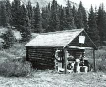 View of the main entrance to the Divide Warden Cabin, showing the off-centered entrance porch with verandah deck, 1981.; Agence Parcs Canada / Parks Canada Agency, 1981.