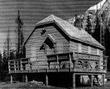 Corner view of the Windy Lodge Warden Cabin, showing the wooden deck which wraps around the building on two sides, ca. 1990.; Parks Canada Agency / Agence Parcs Canada, ca./vers 1990.