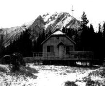 Front elevation of the Windy Lodge Warden Cabin, showing the small gable supported by wooden brackets sheltering the front door, ca. 1990.; Parks Canada Agency / Agence Parcs Canada, ca./vers 1990.