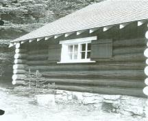 Side elevation of the Bryant Creek Warden Cabin, showing its use of wood construction with round logs laid horizontally, c.1990.; Agence Parcs Canada / Parks Canada Agency, c. 1990.