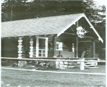Corner view of the Bryant Creek Warden Cabin, showing its three log, tie-beam support system evident in the front porch, c. 1990.; Agence Parcs Canada / Parks Canada Agency, c. 1990.