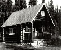 General view of the Egypt Lakes Warden Cabin, showing its wood construction with round logs laid horizontally with saddle-notched corners, 1990.; Agence Parcs Canada / Parks Canada Agency, 1990.