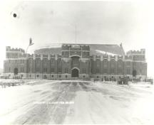 General view of the Mewata Armoury, showing the rugged battlemented façade of stone and red sandstone distinguished by its central ogee-arched troop door, 1918.; Library and Archives Canada / Bibliothèque et Archives Canada