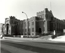 Corner view of the Mewata Armoury, showing one of the four large square, crenelated, three-storey, bastion like corner towers linked by continuous crenelated exterior walls, 1983.; Department of National Defence / Ministère de la Défense nationale, 1983.