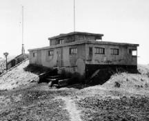 Rear view of the Battery Command Post, showing the reinforced concrete walls, the slightly projecting reinforced concrete splinter-proof roof and the concrete access stairway, ca. 1945.; Department of National Defence / Ministère de la Défense nationale, 1945.