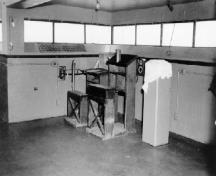 Interior view of the Battery Command Post, showing the Battery Commander's desk and depression rangefinder pedestal, ca. 1945.; Department of National Defence / Ministère de la Défense nationale, 1945.