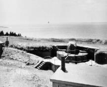 View of the Gun Emplacement, Magazine and Crew Shelter 2, showing the crew shelter building in the foreground, c. 1945.; Ministère de la Défense nationale / Department of National Defence.