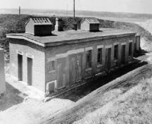 Corner view of the Oil Stores and Artificers Shop, showing the brick walls and slightly pitched roof, ca. 1945.; Department of National Defence / Ministère de la Défense nationale, ca./vers 1945.