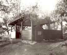 View of the exterior of the Adelaide Island Picnic Shelter, showing the open design and unpartitioned interior space, 1992.; Parks Canada Agency / Agence Parcs Canada / Historica Resources Ltd., 1992.