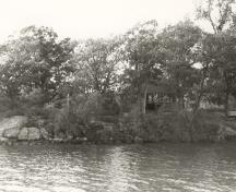 View of the Adelaide Island Picnic Shelter from the river, showing its relatively isolated island location on a heavily treed site, 1992.; Parks Canada Agency / Agence Parcs Canada / Historica Resources Ltd., 1992.