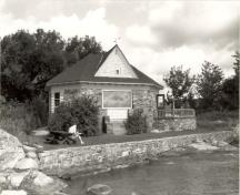 View of the Mallorytown Landing Pavilion, showing its location on a rocky bluff overlooking the St. Lawrence River, 1992.; Agence Parcs Canada / Parks Canada Agency, 1992.