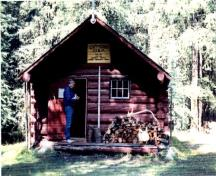 View of the front entrance of the Cuthead Warden Cabin, showing a low-pitched roof, gabled ends and a sheltered off-centered entrance porch with verandah, 1996.; Parks Canada Agency / Agence Parcs Canada, 1996.