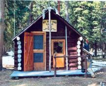View of the main entrance to the Sandhills Warden Cabin, showing the entrance door to one side counterbalanced by a window, 1996.; Agence Parcs Canada / Parks Canada Agency, 1996.