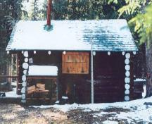 Side elevation of the Sandhills Warden Cabin, showing the rustic round-log wood construction style with saddle-notched corners, 1996.; Agence Parcs Canada / Parks Canada Agency, 1996.