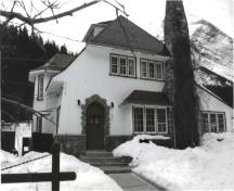Front elevation of the Superintendent's Residence, showing the combination of rough-finished stucco with woodwork and stone, ca. 1991.; Agence Parcs Canada / Parks Canada Agency, ca./vers 1991.