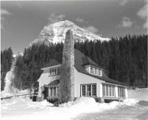 Side elevation of the Superindendent's Residence, showing the steeply pitched hipped-roof and massive, irregularly placed fieldstone chimney, ca 1965.; Agence Parcs Canada / Parks Canada Agency, ca./vers 1965.