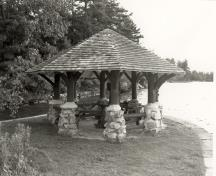 General view of the Gazebo, showing its octagonal, shingled roof, its rubble-stone piers, and its peeled-log posts and brackets, 1992.; Parks Canada Agency / Agence Parcs Canada / Historica Resources Ltd., 1992.