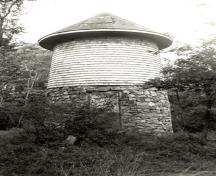 General view of the Water Tower, showing its tapered cylindrical shape, low-pitched conical roof, cedar-shingle cladding and rubble-stone base, 1992.; Parks Canada Agency / Agence Parcs Canada / Historica Resources Ltd., 1992.