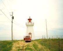 View of Point Bonaventure Light Tower, showing its tapered silhouette and octagonal lantern, 1992.; Agence Parcs Canada / Parks Canada Agency, 1992.