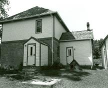 Rear view of the Defensible Lockmaster's House, showing the enclosed east porch and the summer kitchen, 1989.; Parks Canada Agency / Agence Parcs Canada, Couture, 1989.