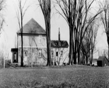 View of the side façade of the Defensible Lockmaster's House, showing the summer kitchen at the rear, 1930.; Parks Canada Agency / Agence Parcs Canada, 1930.