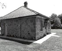 Corner view of the Defensible Lockmaster's House, showing the hipped roof and the original roof framing and the chimney, 1989.; Parks Canada Agency / Agence Parcs Canada, Couture, 1989.
