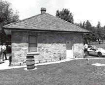 Rear view of the Defensible Lockmaster's House, showing the exterior thick limestone walls, constructed of rough-faced masonry blocks, 1989.; Parks Canada Agency / Agence Parks Canada, Couture, 1989.