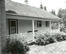 Façade of the Defensible Lockmaster's House, showing the single-storey clapboard addition with full-length verandah, 1989.; Parks Canada Agency / Agence Parcs Canada, Couture, 1989.