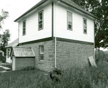 Corner view of the Defensible Lockmaster's House, showing the frame second-floor clad in clapboard, 1989.; Parks Canada Agency / Agence Parcs Canada, Couture, 1989.