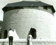 View of the western façade of Murney Martello Tower, showing the limestone walls and the round arched 'carronade porte' openings fitted with iron shutters, 1991.; Parks Canada Agency / Agence Parcs Canada, 1991.