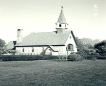 Side view of the Memorial Chapel, showing the simple steeple set on the roof just behind the main entrance, and the steeply pitched copper roof with bell-cast eaves, 1991.; Canadian Parks Service, Atlantic Regional Office/ Service canadien des parcs, Bureau régional de l'Atlantique, 1991.