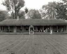 Front view of the Brick Barrack, showing its long rectangular bungalow structure with a prominent low hip roof which sweeps out to cover the long low verandah with its simple support posts, 1990.; Agence Parcs Canada, Bureau Régional de l'Ontario / Parks Canada Agency, Ontario Regional Office, 1990.