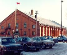 Corner view of the Armoury in Pembroke, showing its load bearing exterior walls clad in red brick with engaged pilasters, 1992.; Department of National Defence / Ministère de la Défense nationale, 1992.