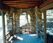 Interior view of the Cambrian Pavilion, showing the stone flagged floor and the plank benches with burl specimens, 1997.; Parks Canada Agency / Agence Parcs Canada, 1997.