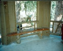 Interior view of Devonian Pavilion, showing the flag stone floor and the burl specimens utilized for the tie beams and bench legs, 1997.; Agence Parcs Canada / Parks Canada Agency, 1997.