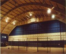 The interior of the hangar space of Hangar 11, showing the west interior elevation with the aircraft doors that are lower than the other elevations with aircraft doors,  2001.; Agence Parcs Canada / Parks Canada Agency, E. Tumak, 2001.