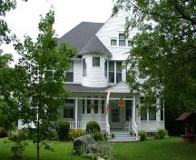 Formal frontal orientation of the house to Maple Street including surrounding grass yard.; PNB 2005