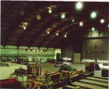 The interior hangar space of Hangar 14, showing the west interior elevation on the right where the aircraft door is situated, and the south interior elevation on the right, 2001.; Agence Parcs Canada / Parks Canada Agency, E. Tumak, 2001.