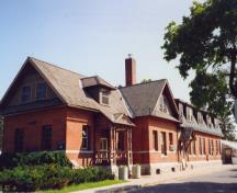 View of the exterior of the Cereal Crops Building, showing the composition and detailing of the front porch, in particular, the turned posts, 1995.; Parks Canada Agency / Agence Parcs Canada, 1995.