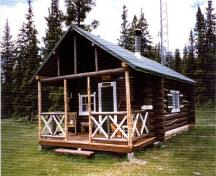 Corner view of Isaac Creek Warden Cabin, showing the main entrance and the open porch projecting from the front, 1996.; Parks Canada Agency/ Agence Parcs Canada, 1996.