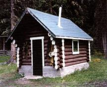 View of the Jacques Lake Warden Cabin Tack Shed; showing the main entrance, side façade and the gabled roof with chimney.; Parks Canada Agency/ Agence Parcs Canada, 1996.